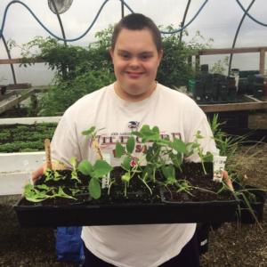 Happy student holding plants
